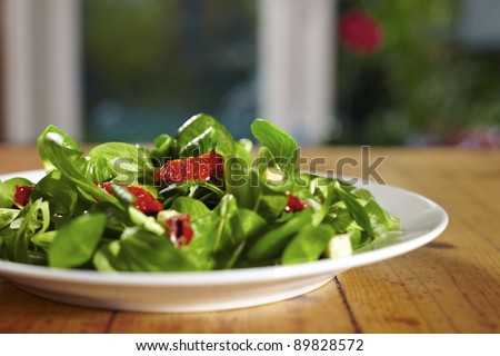 Corn salad plate with dried tomatoes in front of window - stock photo