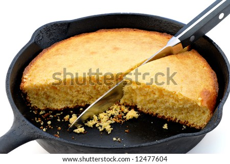 Cornbread in a cast iron skillet against a white background. - stock photo