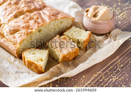 Cornbread squares with peanut butter, paper, wood background