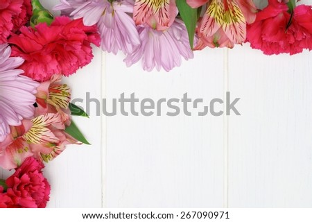 Corner border of pink carnation, daisy and lily flowers against a white wood background - stock photo