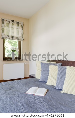 Corner of a creamy bedroom with a large bed covered with blue bed spread in the foreground