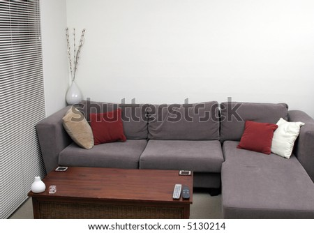 Corner Of A Living Room - Wooden Table, Sofa, Cushions - stock photo
