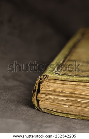 Corner of a vintage book on a dark background. Shallow depth of field. - stock photo
