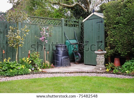 Corner of an English back Garden with shed, compost bin and wheelbarrow - stock photo