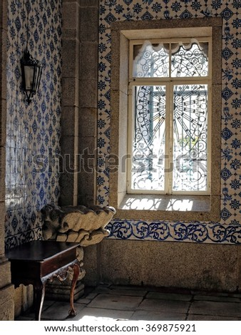 Corner of an old European Catholic church (Porto, Portugal) with a granite baptismal font and beautiful painted tiles on the wall, illuminated by filtratede light from a glass window. High ISO photo. - stock photo