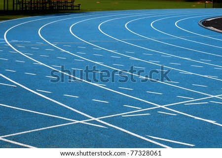 Corner of blue running track - stock photo
