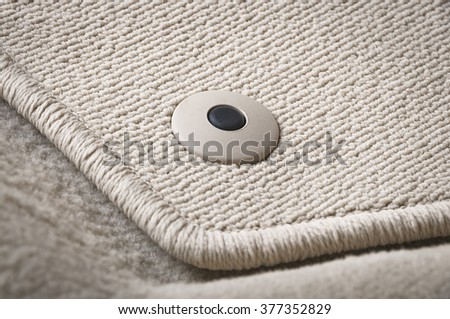 Corner of car mat with floor holder in white car interior - stock photo