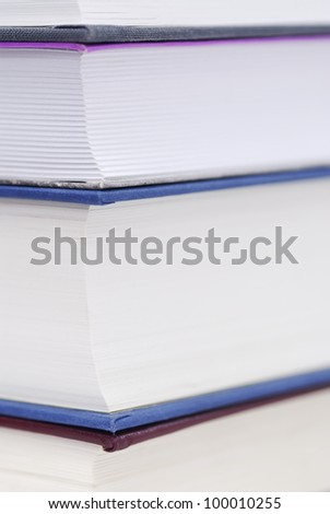 Corner of four books stacked. Copy space, focus on top left pages.