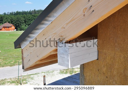 Corner of house with eaves, rafters, truss against summer background. Install softies and roof insulation detail. - stock photo