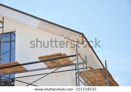 Corner of house with eaves, rafters, truss. Install softies and roof insulation detail. Roofing.