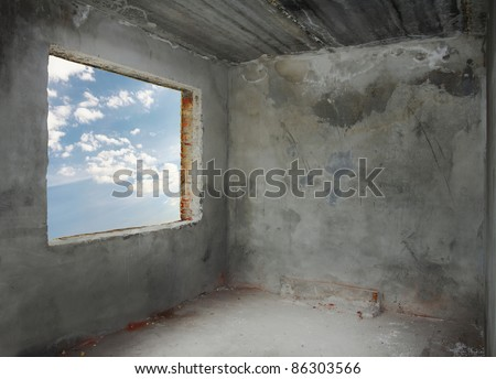 corner of old concrete room with blue sky window - stock photo