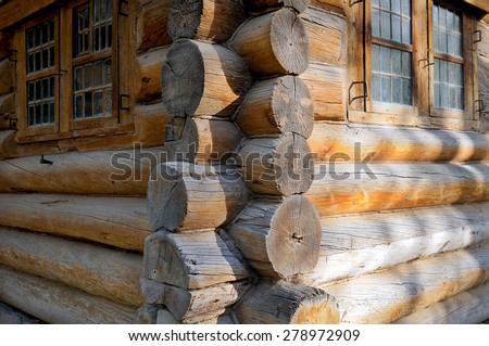 Corner of Russian old wooden house made of logs and window in a wooden frame with small glasses - stock photo