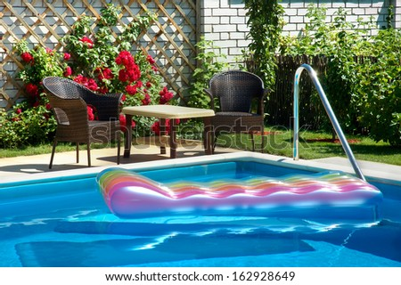 Corner of the pool with blue water and colorful inflatable mattress. In the background, garden furniture, bush of bright red roses and lush greenery. - stock photo
