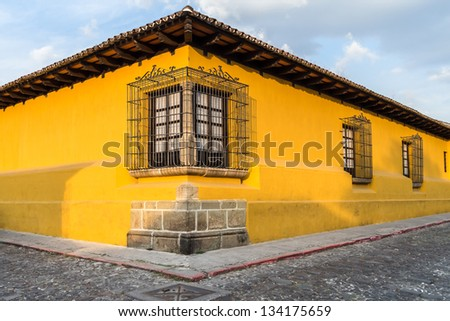 Corner perspective of a bright yellow colonial house with barred windows in Antigua, Guatemala. - stock photo