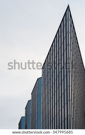 Corner section of modern glass and steel business building - stock photo