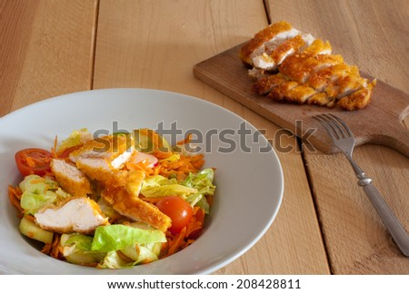 Cornflake crusted chicken pieces served with vegetable salad  - stock photo