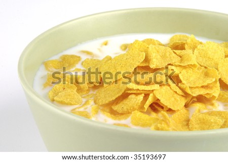 cornflakes and milk in bowl over white