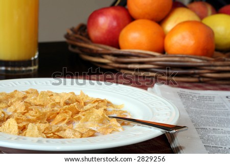 Cornflakes and milk, juice and fresh fruit, and a newspaper.