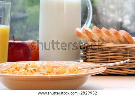 Cornflakes and milk, juice, fruit and freshly sliced bread. Shallow depth of field, focus on the cornflakes.