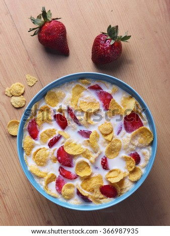 Cornflakes cereal and strawberry bowl for breakfast on blue bowl - stock photo