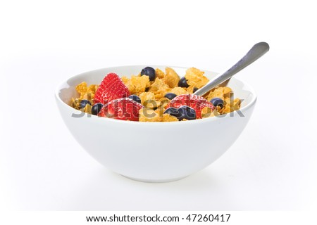 Cornflakes cereal with strawberries and blueberries in a white bowl isolated over white - stock photo