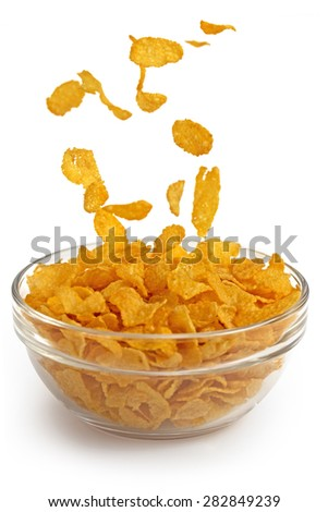 cornflakes falling into a glass bowl on white background - stock photo