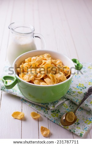 Cornflakes in bowl with milk  on wooden background. Selective focus.