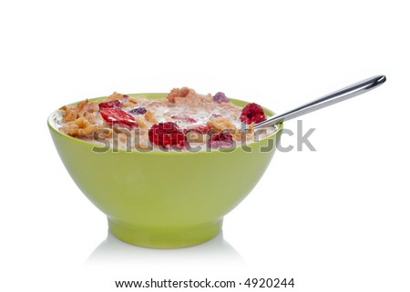 Cornflakes of fruits with the spoon inside the green bowl, reflected on white background. Shallow DOF - stock photo