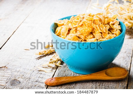 cornflakes on wooden table at morning - stock photo