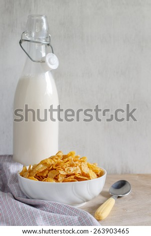 cornflakes served in white cup with fresh milk put on vintage white wood - stock photo