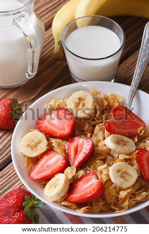 Cornflakes with fresh strawberries and a banana on the table and milk in a glass closeup. vertical  - stock photo