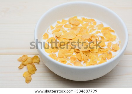 cornflakes with milk in old white bowl on  wooden table - stock photo