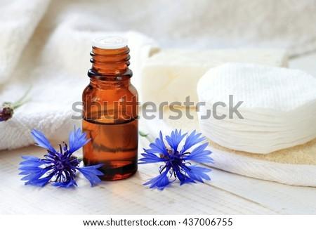 Cornflower herbal tincture. Dark glass apothecary bottle, white towels, cotton pads, fresh blue flowers. Holistic facial skincare. Prevent dark under eye circles. - stock photo