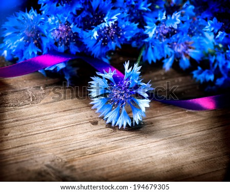 Cornflowers. Wild Blue Flowers Blooming. Over wooden background. Closeup Image. Soft Focus - stock photo