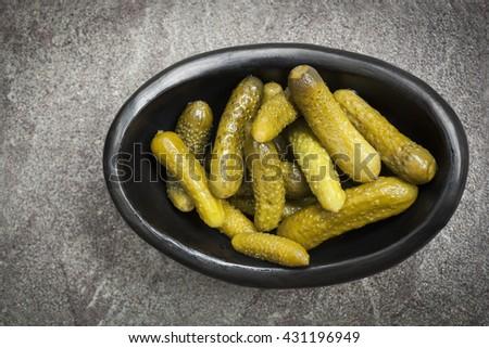 Cornichons in black dish on slate.  Top view. - stock photo