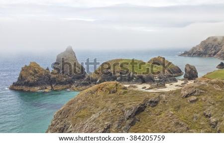 Cornish coastline panorama near Kynance Cove with sandy beach, turquoise sea, rugged rocks  on a summer foggy day, Cornwall, Lizard, Peninsula, south west England - stock photo