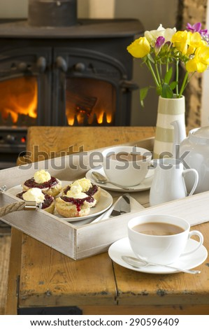 Cornish Cream Tea with home made scones topped with Cornish clotted cream and strawberry jam on a wooden tray