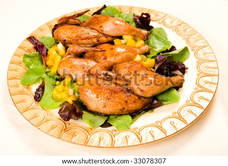 Cornish hen halves served on a bed of lettuce with mango salsa