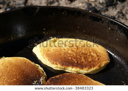 Cornmeal pancakes cooking in a cast iron skillet over an open fire outdoors. Close up view of cakes - stock photo