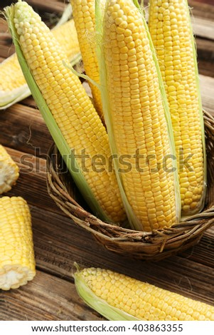 Corns in basket on a brown wooden background - stock photo