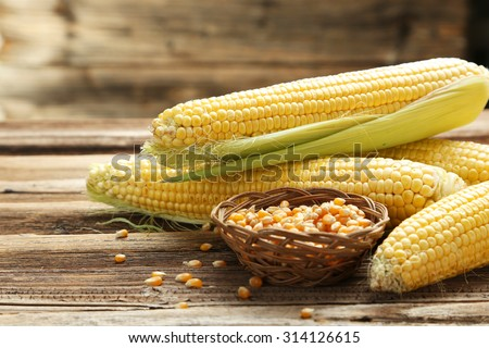 Corns on a brown wooden background - stock photo