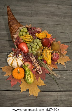 Cornucopia filled with fall harvest spilling out of it's horn of plenty