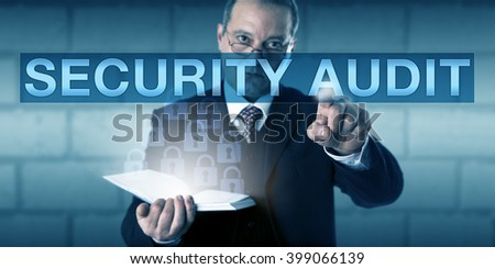 Corporate auditor is touching the term SECURITY AUDIT on a transparent screen. The man is looking across his spectacles with a concentrated expression. Business and information technology concept. - stock photo