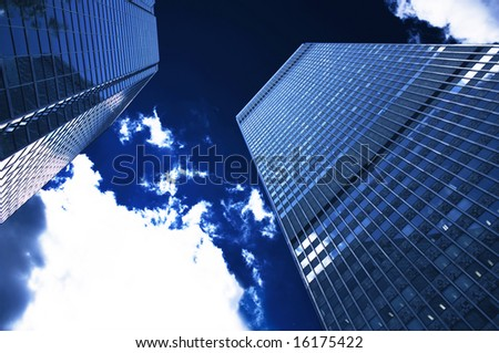 Corporate building on a dark blue sky with cloud - stock photo
