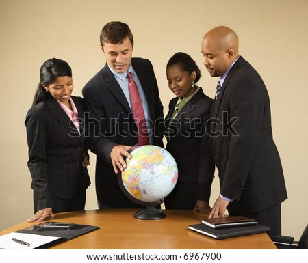 Corporate businesspeople standing around world globe smiling and talking.