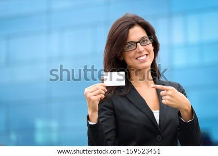 Corporate businesswoman showing white empty business card. Female hispanic caucasian executive outside. - stock photo