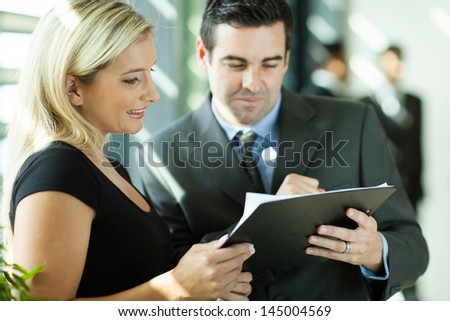 corporate colleagues looking at monthly report - stock photo