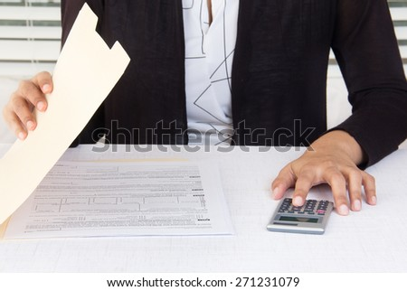 Corporate employee dressed in black suit at workplace is opening a folder and calculating financial data using a calculator.  Office desk is infront of a window with white blinds.  - stock photo