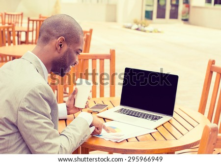 Corporate employee young businessman working outdoors on summer day, reading documents using laptop computer drinking coffee - stock photo
