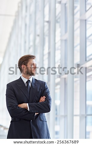 Corporate executive in a modern architectural setting looking confidently out of high rise windows - stock photo